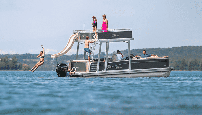 A double decker pontoon boat with people enjoying the slide from its top level