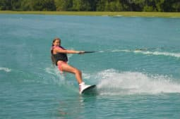 A woman wake boarding over the calm water