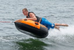 A man having fun out on the water using a large inflatable ring